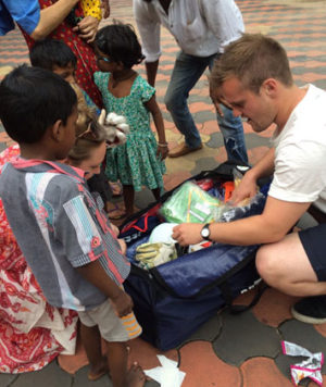 Ben Dickinson handing over some equipment to children in an orphanage in India.